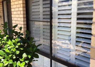 White plantation shutters inside a window